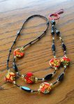Beaded Lanyard: black with golden amber and tomato-red hues accents. Floral motif shell beads, 8mm black Jasper round beads, black seed beads (some Vintage Venetian) along with black accent beads