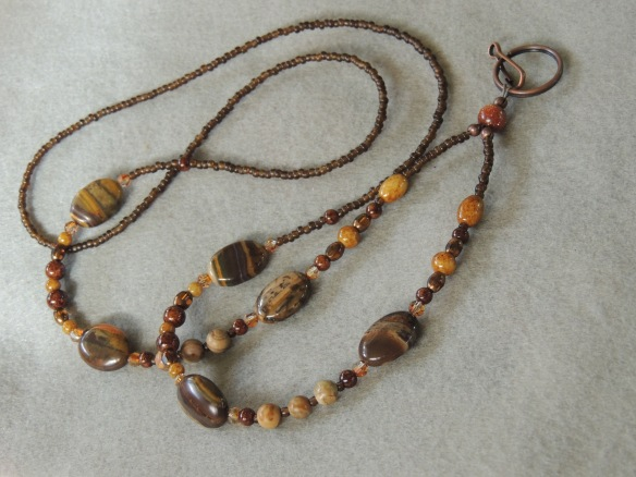 Lanyard with petrified wood, Swarovski crystals, Vintage Venetian sepia seed beads, Chinese Picture Jasper rounds, and a variety of glass seed beads in shades of brown. This one sparkles!