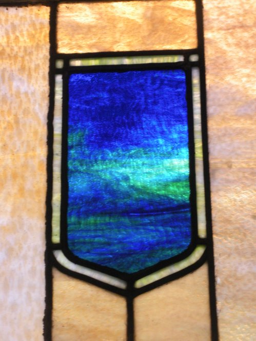 This particular stained glass piece reminds me of a watercolor landscape painting.